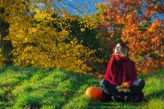 红色衣裳的年轻红头发人女孩坐台阶 库存图片
