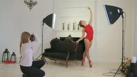 红色衣裳的年轻美丽的芭蕾舞女演员,红色身体和红色pointe在聚光灯下和在减速火箭的沙发附近在黑色 影视素材