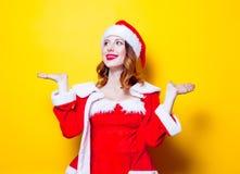 红色衣裳的年轻圣诞老人Clous女孩 免版税库存照片
