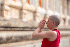 红色衣裳年轻修士致敬尊敬在佛教寺庙公园  免版税图库摄影
