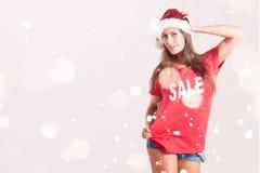 红色衬衣和圣诞老人帽子的美丽的妇女 库存图片