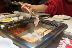 红色衬衣妇女烹调中国shabu hotpot,美味 免版税库存照片