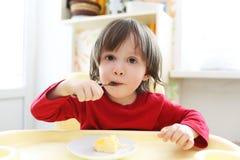 红色衬衣的小孩吃煎蛋卷的 免版税库存照片
