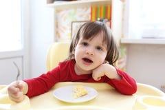 红色衬衣的小孩用煎蛋卷 免版税库存照片