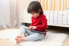 红色衬衣的小男孩有片剂计算机的 免版税库存照片