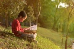 红色衬衣的年轻亚裔男孩读书的在湖庭院附近 免版税库存图片