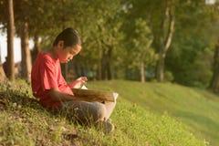 红色衬衣的年轻亚裔男孩读书的在湖庭院附近 库存图片
