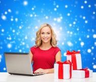 红色衬衣的微笑的妇女有礼物和膝上型计算机的 库存照片