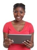 红色衬衣的笑的非洲妇女有片剂的 库存照片