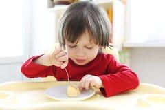 红色衬衣的逗人喜爱的小孩吃煎蛋卷的 免版税库存照片