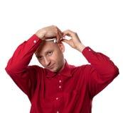 红色衬衣的年轻人投入electroencephal顶头的耳机EEG 库存照片