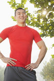 红色衬衣身分和微笑的年轻肌肉人,户外在一个公园在北京 免版税库存图片