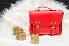 红色袋子和微型礼物盒在白色毛皮 时兴的概念 Hol 库存图片