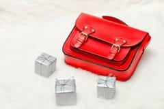 红色袋子和微型礼物盒在白色毛皮 时兴的概念 Hol 免版税库存图片