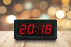 红色被带领的光阐明了在数字式电闹钟面孔的第2018年在与defocused五颜六色的Chri的棕色木台式 免版税库存照片