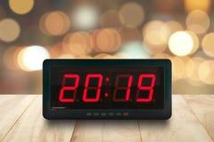 红色被带领的光阐明了在数字式闹钟面孔的第2019年在与defocused五颜六色的圣诞灯bokeh的木桌上 库存照片