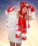 红色被编织的衣裳的一个少妇拿着有一个蜡烛的一个灯笼 免版税库存图片