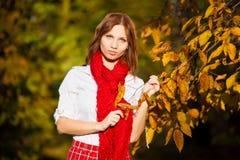 红色裙子、白色女衬衫和围巾的女小学生 库存图片
