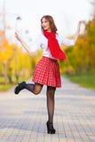红色裙子、白色女衬衫和围巾的女小学生 库存照片