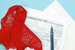 红色裤子、皮带、空的联邦税务局报税表1040和笔一张顶上的照片  整体税概念,破产 大税的概念 免版税库存图片
