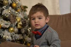 红色裤子和蝶形领结的一个男孩 免版税图库摄影
