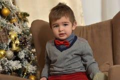 红色裤子和蝶形领结的一个男孩 库存照片