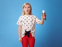 红色裤子的惊奇的现代女孩在蓝色显示的杀虫药 免版税库存照片