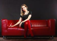 红色裤袜的时尚妇女在长沙发 库存照片