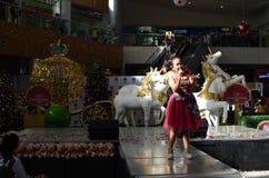 红色褂子的女孩唱歌在购物中心的圣诞节介绍时的 免版税库存图片
