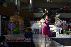 红色褂子的女孩唱歌在购物中心的圣诞节介绍时的 库存图片