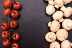 红色西红柿和蘑菇蘑菇在一个石黑板,背景说谎 免版税库存照片