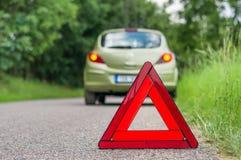 红色警告三角和残破的汽车在路 库存图片