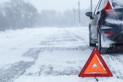 红色警告三角特写镜头与一辆失败的汽车的在冬天 免版税库存图片