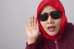 红色认真听的回教夫人,在耳朵的手 库存照片