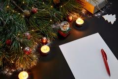 红色说谎在黑背景顶视图的绿色云杉的分支附近的圣诞节球和笔记本 文本的空间 免版税库存图片