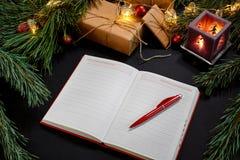 红色说谎在黑背景顶视图的绿色云杉的分支附近的圣诞节球和笔记本 文本的空间 库存图片