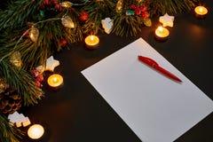 红色说谎在黑背景顶视图的绿色云杉的分支附近的圣诞节球和笔记本 文本的空间 库存照片