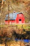 红色谷仓和小河 库存照片