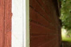 红色谷仓墙壁的Artsy射击的关闭有白色修剪的 库存照片