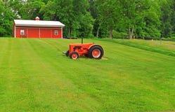 红色谷仓拖拉机绿色草坪 库存照片