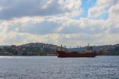 红色货船通过博斯普鲁斯海峡进入黑海 免版税图库摄影