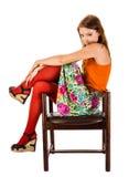 红色贴身衬衣的女孩在一把老木椅子坐 免版税图库摄影