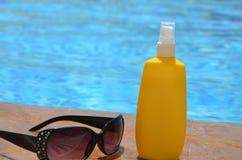红色赤素馨花羽毛开花,太阳镜、海滩帽子和蓝色毛巾在游泳池的边 假期,海滩 免版税库存图片