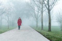 红色走的少妇由雾的城市公园 免版税库存图片