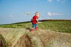红色起动的男孩走在干草捆的 免版税库存图片