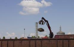 红色起重机投掷的金属工业废料到在火车站的一个火车容器里|烟囱 库存图片