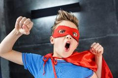 红色超级英雄服装打手势的小男孩 免版税库存照片