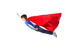 红色超级英雄海角和面具飞行的男孩在空气 免版税库存图片