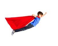 红色超级英雄海角和面具飞行的男孩在空气 库存图片