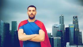 红色超级英雄海角的人在城市背景 免版税库存照片